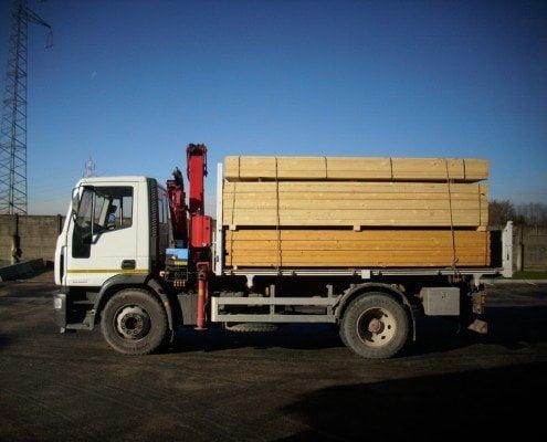 Camion carico di bancali con travi in legno
