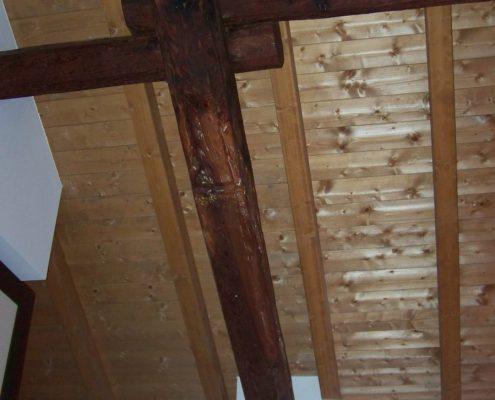 Travi antiche che sostengono tetto in legno moderno